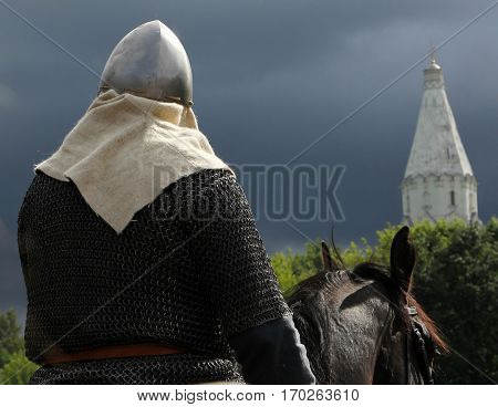 Horseman in armor on a background of church and stormy sky