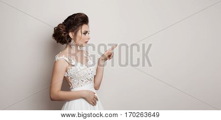 Portrait of bride in wedding dress gesturing by finger at side looking away. Side view of brunette girl posing at studio pointing and presenting something by hand to side. White studio background.