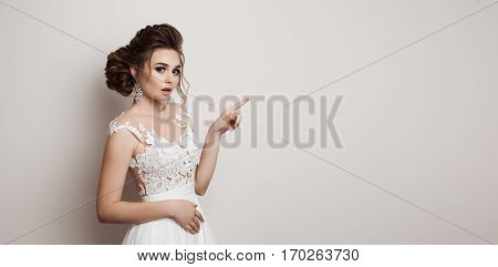 Emotional bride in white dress shocked looking at camera with opened mouth. Beautiful brunette woman with stylish haircut posing gesturing and pointing by finger at side. White studio background.