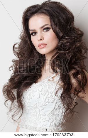 Studio portrait of attractive brunette girl with long wavy hair and stylish haircut wearing white dress with elements of lace. Female with evening make up posing at camera. White background.