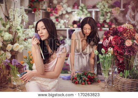 Beautiful asian florist girls making bouquet of flowers on table for sale against floral bokeh background in flower shop indoors. Two attractive asian females florists working in store. 2 playful fashion models in tender dresses posing and looking at came