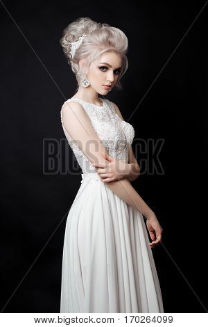 Side view of blonde woman in lace dress posing at studio holding and touching her hands. Bride with stylish haircut shiny earrings and accessories in hair looking and at camera. Black background.