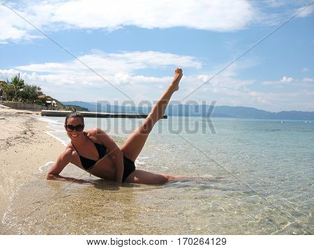 Beautiful young girl on the beach doing yoga exercises against the sunlight.