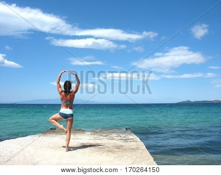 Beautiful young girl on the beach-Yoga practicing