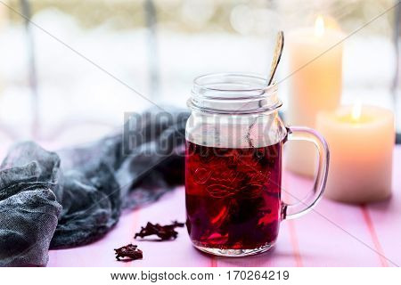Hibiscus tea in glass Cup. The candles in the background. Tea strainer nearby. Light background. Selective focus
