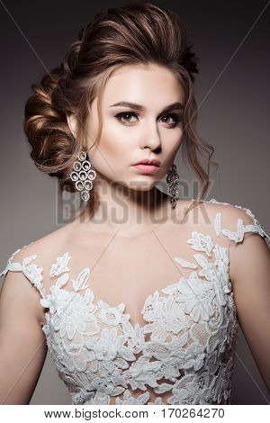 Studio portrait of gorgeous brunrtte woman with stylish haircut and evening make up posing in studio. Female wearing white dress with elements of lace and big earrings. Famale after beauty salon.