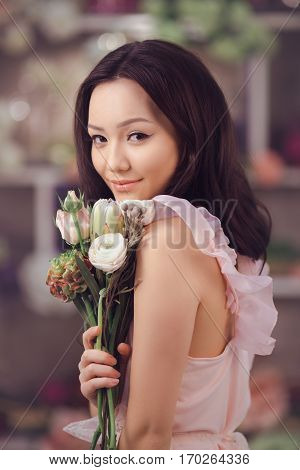 Beautiful girl in tender pink dress with bouquet flowers peonies in hands standing against floral bokeh background in flower shop. Joyful asian female florist. Playful fashion model looking at camera and smiling.