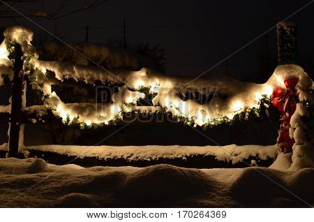 Snow covered evergreen garland draped on a country fence with lights at night