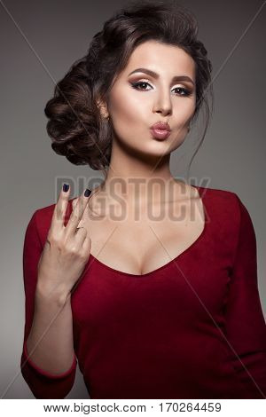 Studio portrait of gorgeous brunette girl gesturing peace sign by fingers and sending air kiss at camera. Woman wearing red dress with big neckline. Brunette with perfect haircut and evening make up.