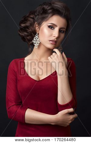 Studio portrait of sensuality brunette girl posing and looking at camera touching chin by hand. Beautiful woman with seductive figure wearing red dress with stylish haircut and big earrings.