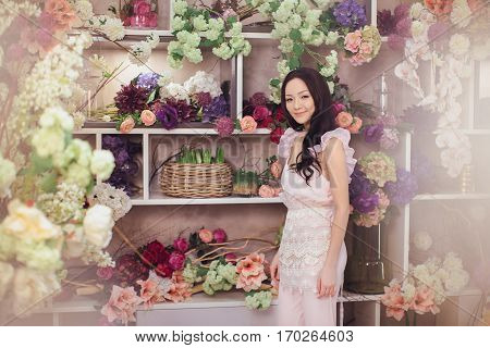 Beautiful girl in tender pink dress standing against floral background in flower shop. Joyful asian female florist with alot of flowers . Playful fashion model looking at camera.