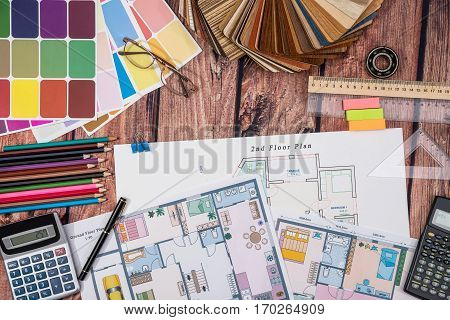 house floor paper plan and wooden sampler work tolls calculator on wooden table.