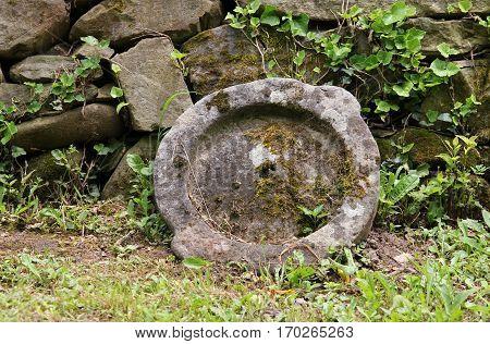 Old millstone on a background of stone wall Etara Bulgaria