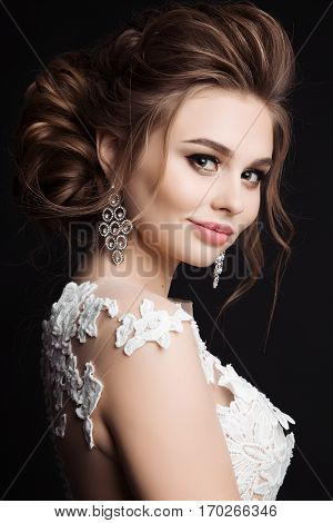 Side view of gorgeous brunette girl posing at studio and smiling at camera. Female wearing white dress and big earrings. Woman after beauty salon with haircut and evening make up.