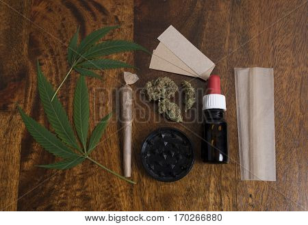 Cannabis sativa leaves and THC oil with grinder and papers to smoke weed joint on wooden background.