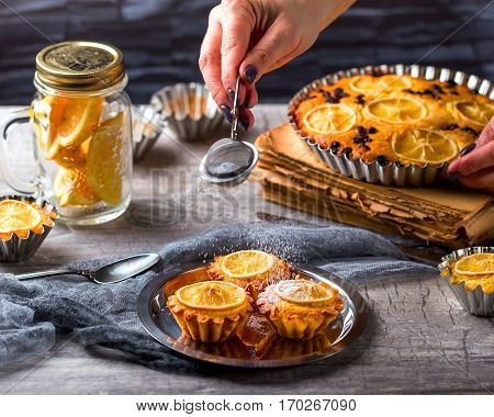 Lemon muffins on a metal dish. Hand sprinkle with powdered sugar a cupcakes . lemon pie and cut lemon in a bowl in the background