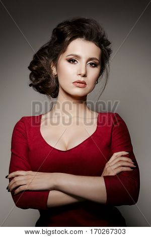 Portrait of confident brunette girl posing with crossed arms at camera. Gorgeous woman wearing in red dress with perfect haircut and evening make up plump lips. Gray studio background.