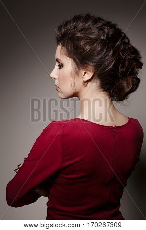 Side view of gorgeous of brunette woman with stylish haircut of curly hair turned back posing with crossed arms. Brunette girl wearing red dress looking down. Gray studio background.