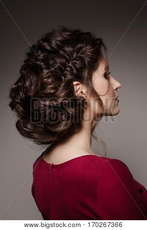 Turned to side gorgeous brunette girl with stylish haircut of curly hair turned back posing with crossed arms. Brunette girl wearing red dress looking away. Studio background.
