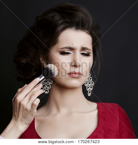 Incognito makeup artist making blush on cheekbone with brush for capricious brunette girl posing with face expression. Unhappy girl with stylish haircut and big earrings and closed eyes. Dark studio.