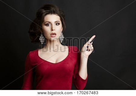 Emotionally woman in red dress pointing by finger at side on wall. Girl with opened mouth shocked looking at camera. Female with big earrings and stylish haircut.