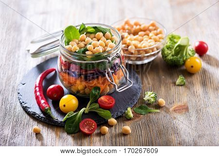 Healthy homemade chickpea and veggies salad in a jar. Diet vegetarian vegan food, clean eating.