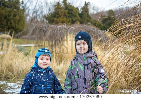 Two Little Kids Boys, Friends Holding Hands And Hugging. Adorable Siblings In Bright Colorful Clothe