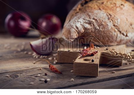 Fresh multigrain crusty bread onion chilly and wheat ears on a rustic wooden table. Bakery and grocery food store concept.