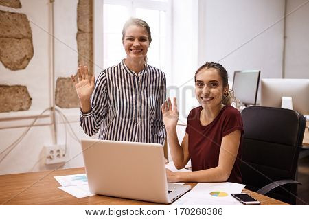 Two Business Women Waving At Camera