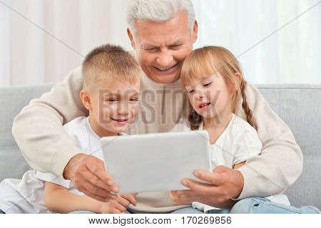 Grandfather with grandchildren using tablet on couch