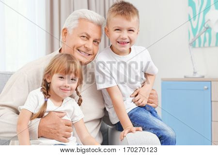 Grandfather with grandchildren sitting on couch