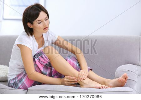 Beautiful young woman suffering from pain in ankle at home
