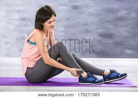 Beautiful young woman suffering from pain in ankle while sitting on stretching mat indoors