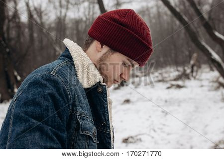 Stylish Hipster Traveler With Backpack In Red Hat  Walking In Winter Snowy Forest. Wanderlust And Ad