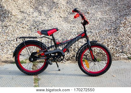 Children Black And Red Bicycle On Gravel Background