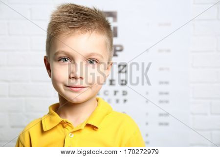 Little boy on ophthalmic test chart background