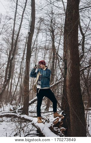 Stylish Hipster Traveler Taking Photo Of Winter Woods, Traveling And Exploring Snowy Forest. Young P