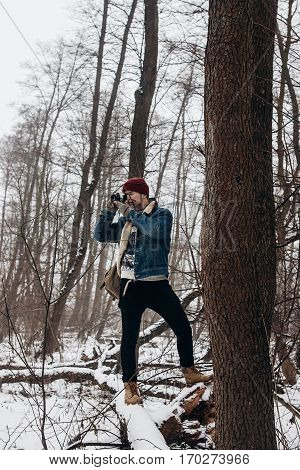 Stylish Hipster Traveler Holding Camera And Making Photo In Snowy Forest. Wanderlust And Adventure C