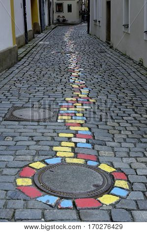 brightly painted cobblestones mark a way direction