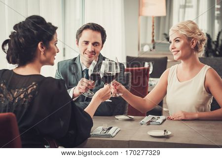 Group of wealthy people clinking glasses of red wine in restaurant.