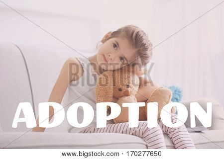 Adoption concept. Little girl with toy sitting on couch at home