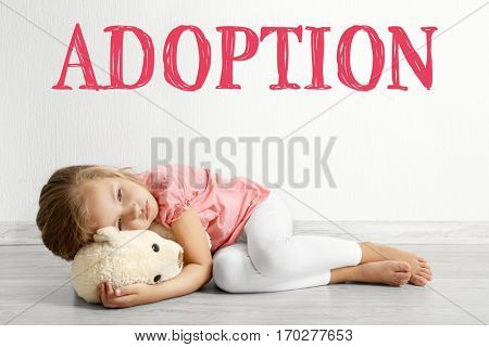 Adoption concept. Sad little girl with toy lying on floor