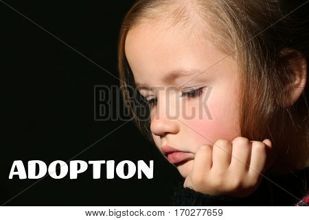 Adoption concept. Sad little girl on black background