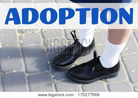 Adoption concept. Little girl in stylish shoes standing on pavement