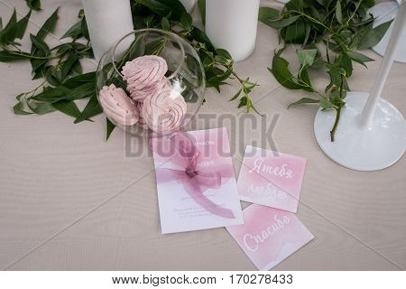 Fluffy pink marshmallow in a glass jar, greenery and wedding cards on the table with pink tablecloth. Text of cards: «I love you», «Thank you»