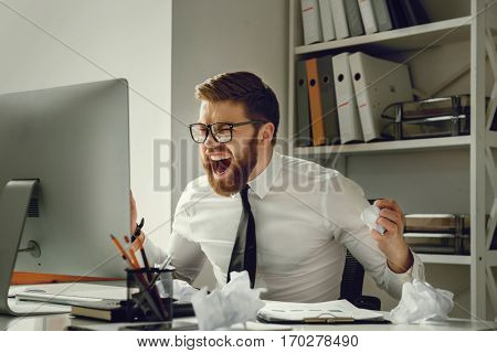 Portrait of a frustrated businessman in panic sitting at his working place