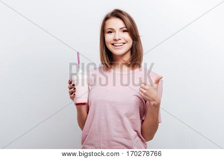 Picture of pretty young lady standing over white background while holding cocktail and make thumbs up gesture