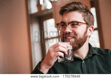 Image of attractive bearded young man wearing glasses sitting in cafe while drinking whiskey.