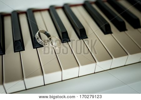 Closeup wedding silver rings lying on the piano keys