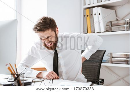 Photo of young businessman with painful feelings sitting in office while holding his back.